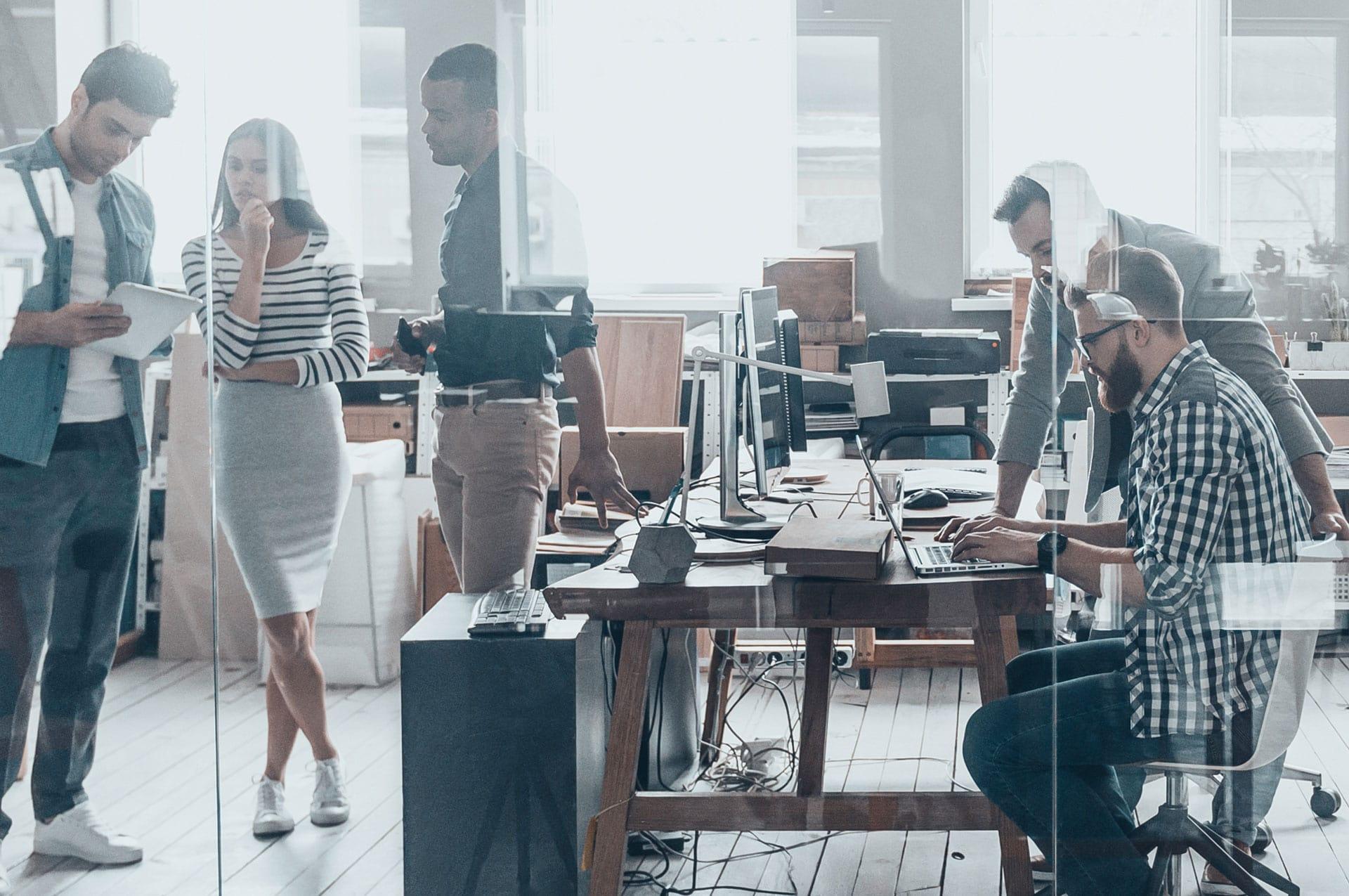 Blick in ein Großraumbüro durch eine Glaswand, viele arbeitende Menschen